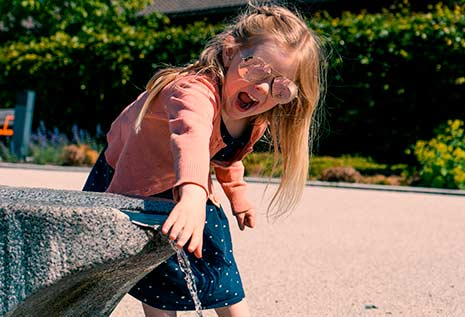 girl wearing sunglasses playing with water