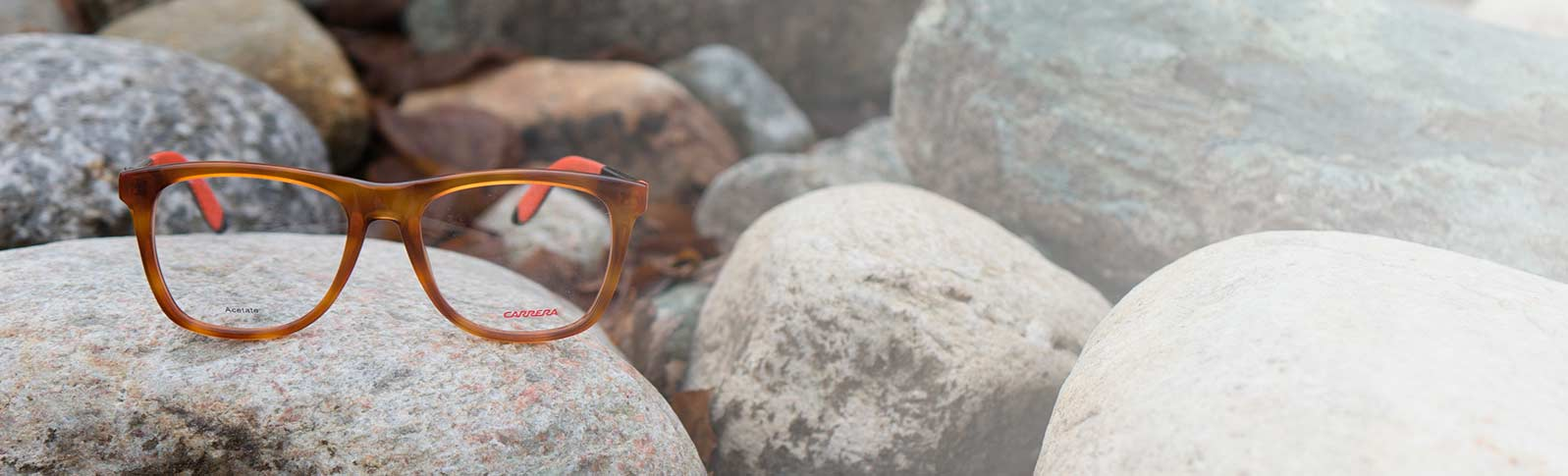 carrera glasses on a bed of gravel and stones