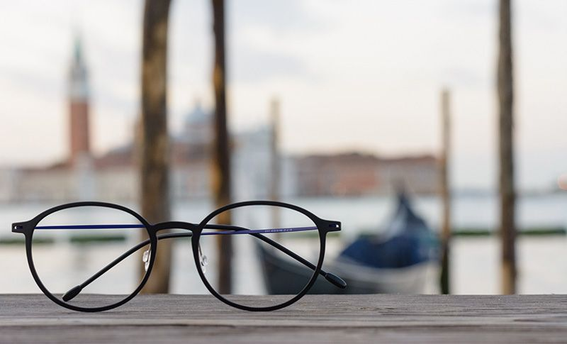 glasses on a table with the ocean in the background